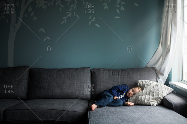 Young boy sleeping on big comfortable couch with a mural of a tree in the background.