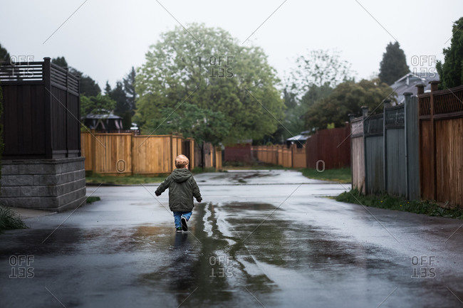 Young boy walking away from camera on a wet rainy street.