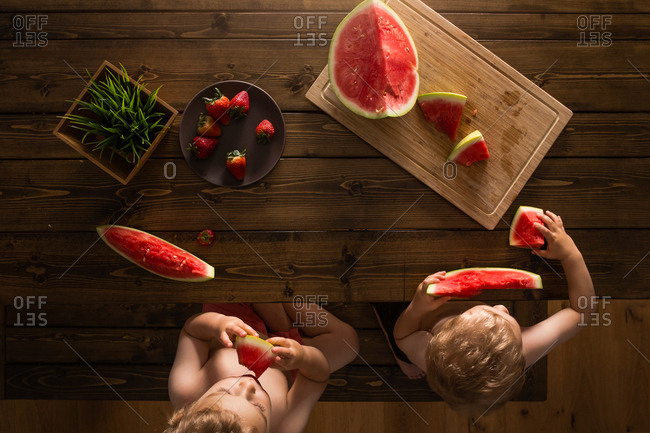 2 boys sitting at a wooden picnic table eating watermelons and strawberries shirtless.