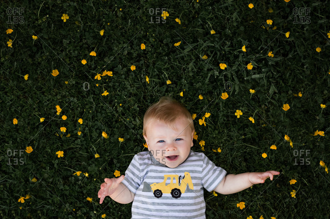 Young boy laying in grassy field with yellow flowers.