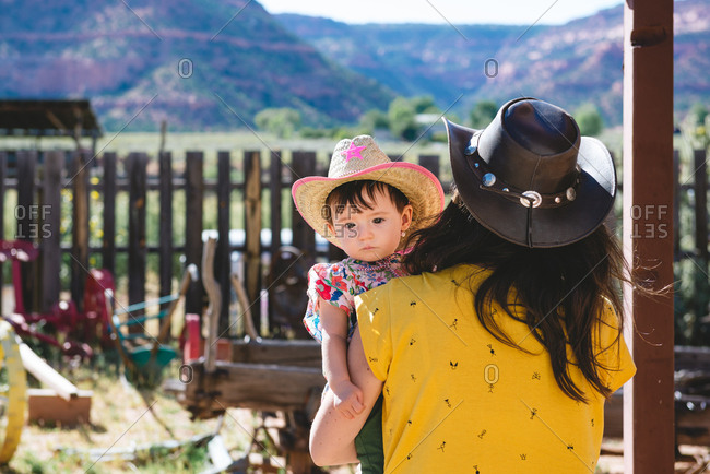 Mother and daughter sit outdoors wearing cowboy hats