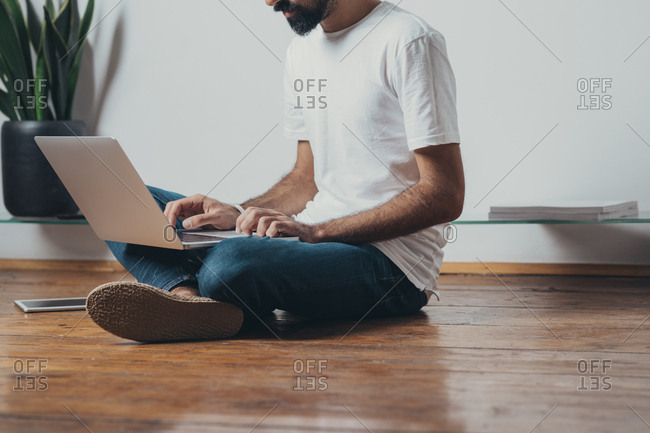 Unrecognizable man freelancer sitting on the floor and typing on her laptop.