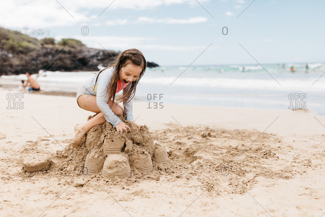 Little girl climbing on top of a sand castle