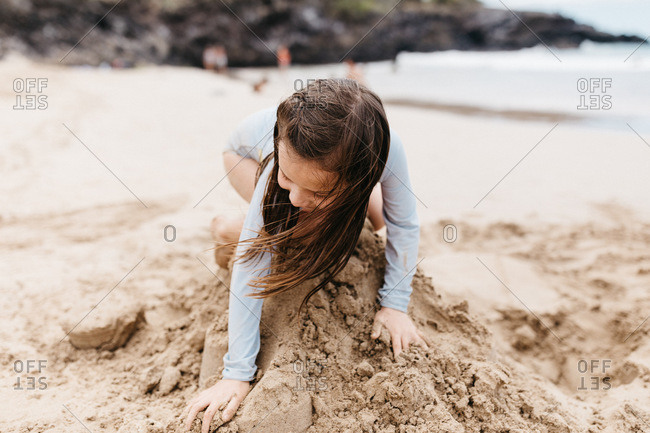 Young girl smashing a sandcastle to the ground