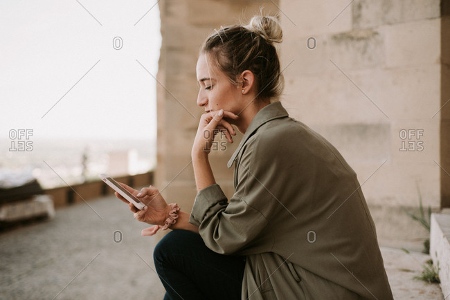 Woman sending a text as she watches the sunset