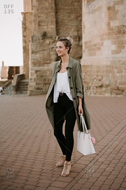 Woman modeling handbag outside of a stone fortress