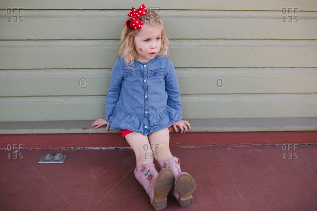 Cute blonde toddler sitting on front porch with rainbow face paint