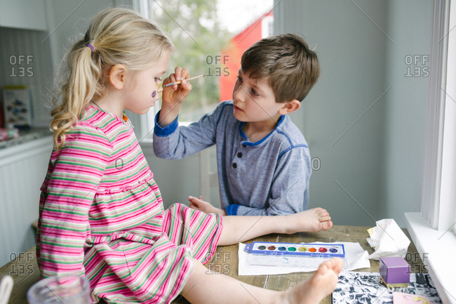 Young boy applying face paint to his sister