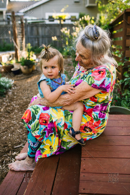 Toddler girl sits on her great gradnmother's lap on a deck in a garden