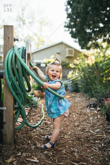 Toddler girl laughs as she swings from a garden hose