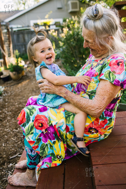 Smiling toddler girl sits on her great grandmother's lap in a garden