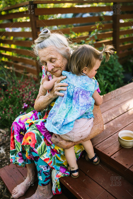 Toddler girl hugs her great grandmother, who sits on a deck in a garden.