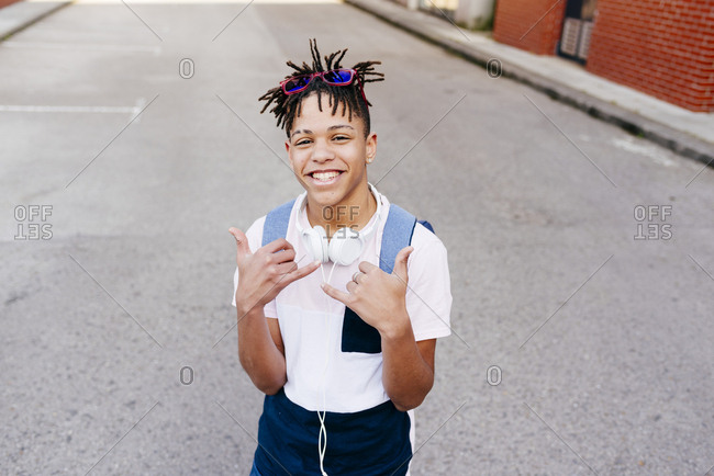 Young joyful African American handsome man in casual apparel with headphones standing on street and showing shaka hand sign