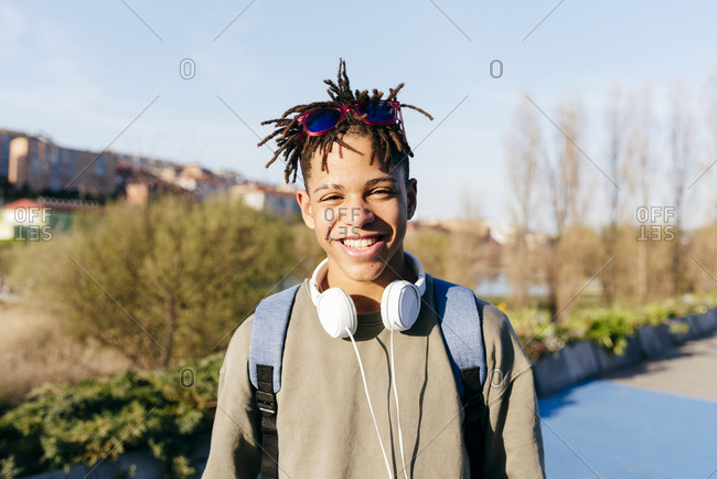 Young African American happy successful man in casual outfit with stylish sunglasses and headset on street looking at camera
