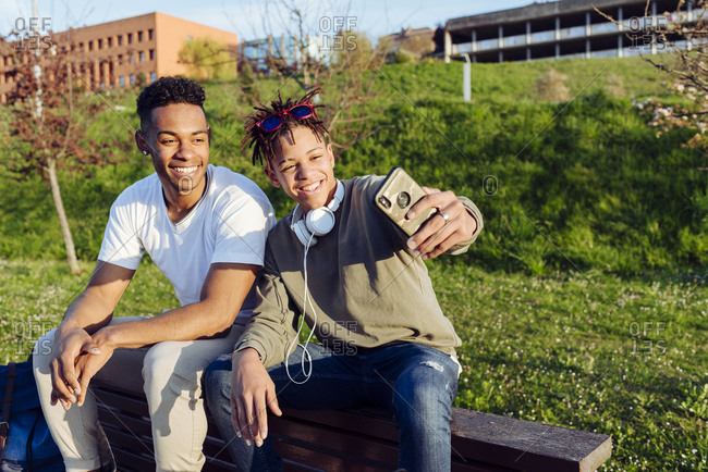 Young black men sitting on bench with smartphone