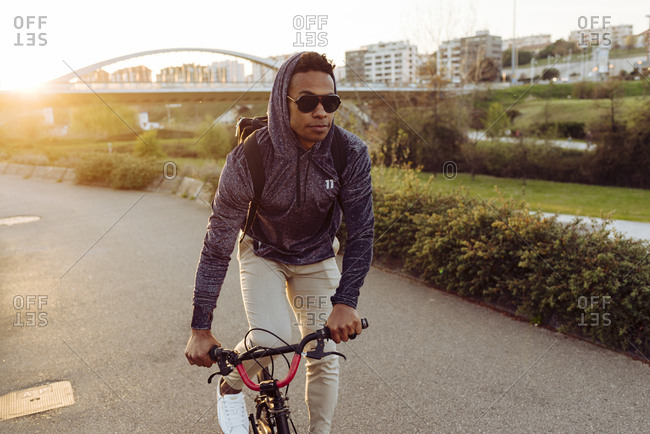 Young African American handsome man in casual outfit and stylish sunglasses riding bicycle near bridge in bright back lit