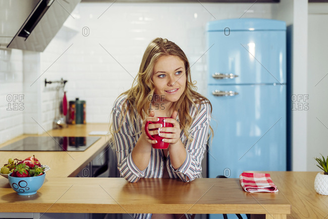 Young woman holding hot tea in kitchen