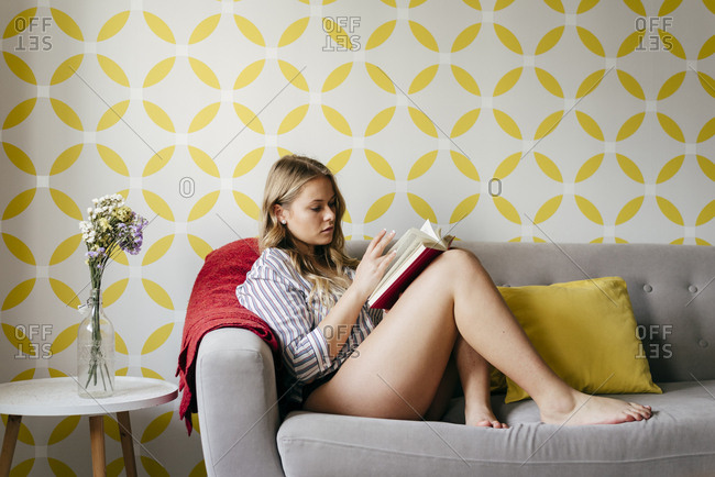 Young happy female reading book on sofa