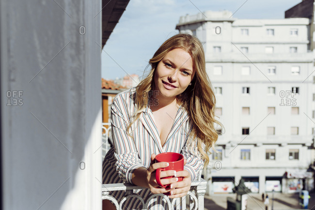 Young sexy cheerful female with cup on terrace