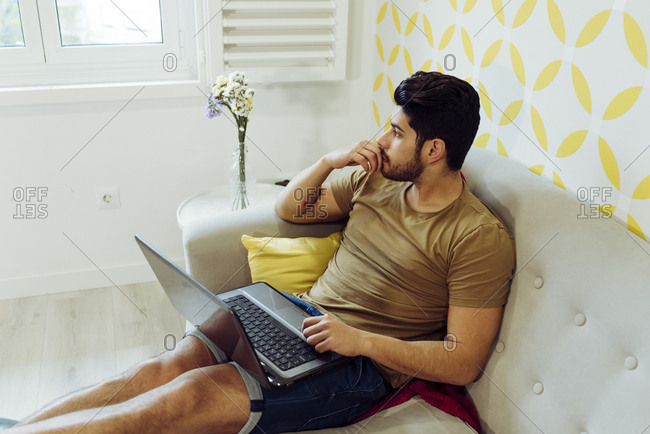 Side view of young thoughtful man in casual outfit with laptop sitting on couch near table with fresh flowers