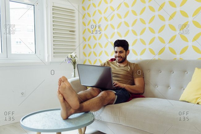 Side view of young cheerful man in casual outfit with laptop sitting on couch near table with fresh flowers
