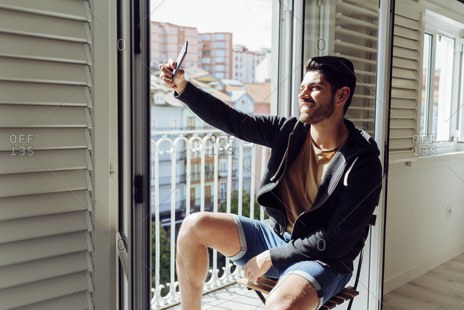 Side view of young joyful successful man in casual apparel sitting on chair near balcony and taking selfie with smartphone