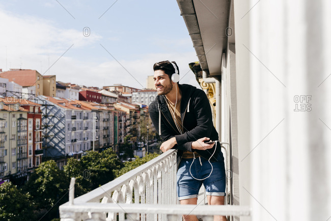 Young smiling handsome casual male in headset leaning on terrace railing with smartphone and looking away