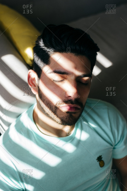 From above young tired depressed alone male in casual shirt sitting on sofa at home and looking at camera