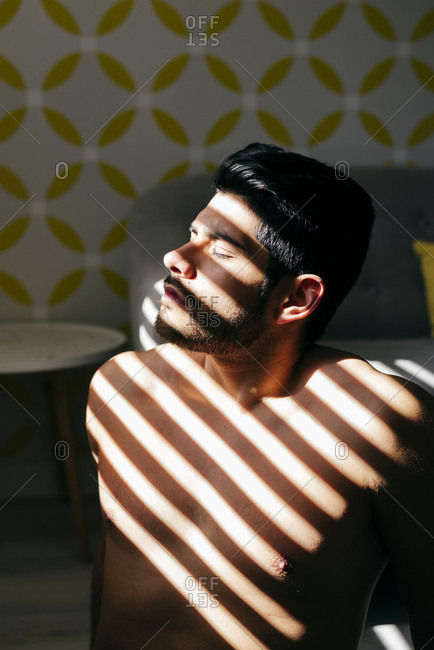 From above young naked handsome male with stylish hairstyle standing near sofa enjoying sunlight with closed eyes