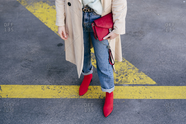 Crop young attractive woman in stylish coat, jeans and red shoes with bright handbag standing on road with kings