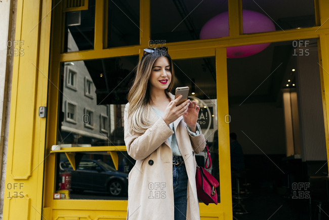 Young cheerful female standing near house with smartphone