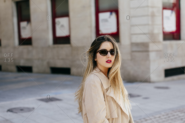 Young woman in sunglasses posing on street
