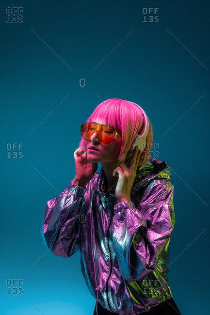 Young Asian woman with stylish pink haircut and sparkly silver jacket standing and listening music
