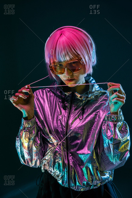 Trendy young Japanese woman with purple hair standing in sparkly silver jacket and red sunglasses on blue background