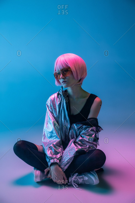 Trendy young Japanese woman with purple hair standing in sparkly silver jacket and red sunglasses sitting on blue background