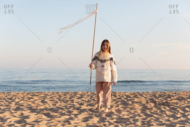 Cheerful female teenager in stylish sweater holding stick with ribbons and looking at camera against cloudless blue sky