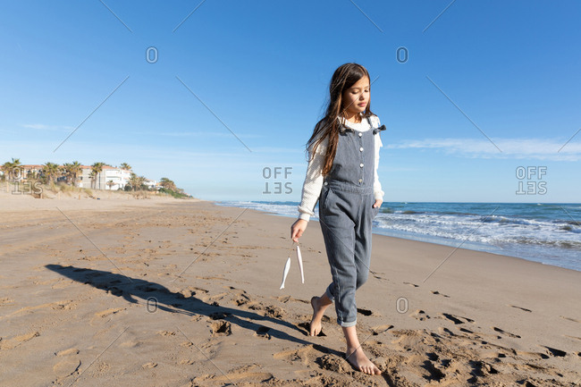 relaxed girl in casual outfit smiling and holding accessory with ribbons while standing on sandy shore near waving sea