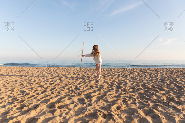 Cheerful female teenager in stylish sweater holding stick with ribbons and looking away against cloudless blue sky