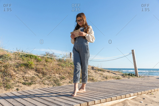 Barefoot girl in casual outfit and glasses reading good book while walking on lumber path on beach near waving sea
