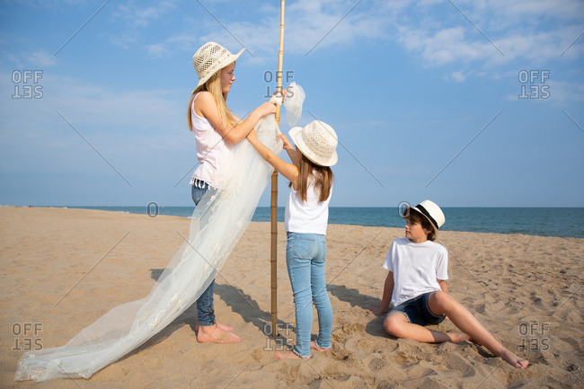 Girls in hats attaching awning on pole while boy sitting on sand on beach
