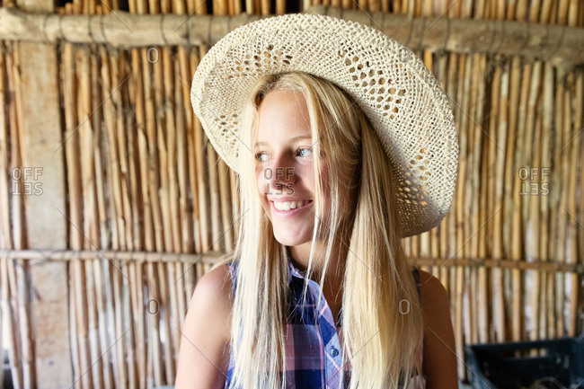Female teenager in straw hat smiling and looking away while standing against wooden partition inside shed on farm