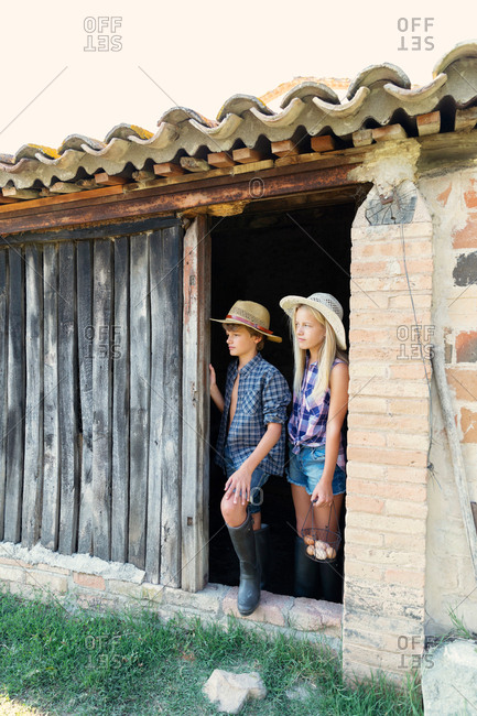 Teen boy and sister standing in barn entrance together on sunny day on farm