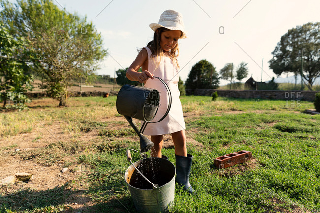 Little girl in dress and hat pouring clean water from can into bucket while standing on farmyard on sunny day