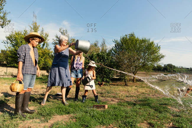 Grandmother splashing water from bucket on lawn while standing near grandchildren on sunny day on ranch