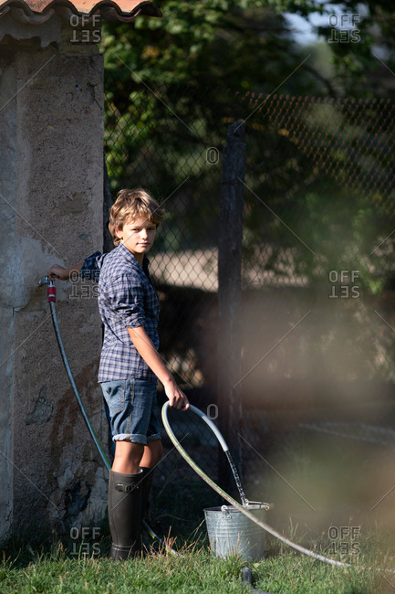 boy pouring clean water into bucket while standing on farmyard on sunny day