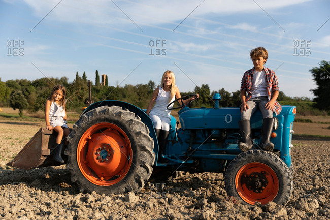 Boy and two girls in casual outfits sitting on blue tractor on sunny day in agricultural field