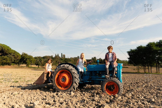 group of young friends siting and looking at camera on a blue tractor in a rural terrain