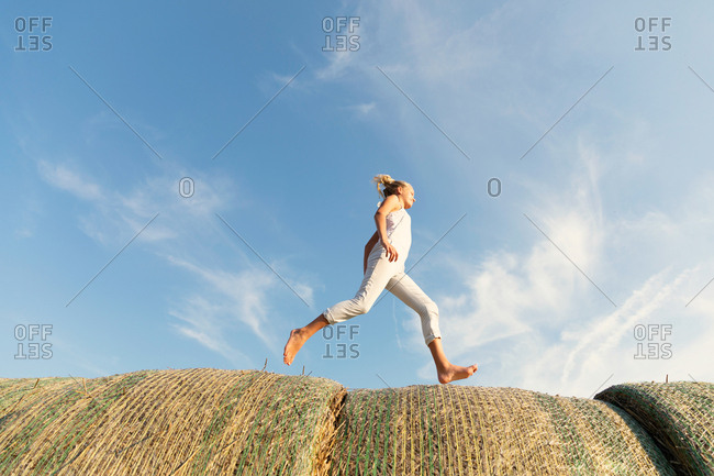 Side view of barefoot girl running on rolls of dried grass against cloudy blue sky on sunny day on farm