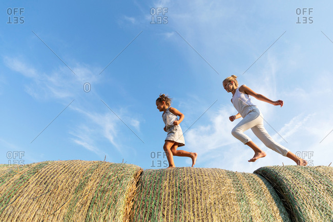 Side view of three kids running on rolls of straw together against cloudy blue sky in agricultural field