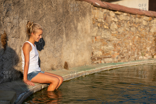 Side view of girl sitting near shabby wall and splashing clean water of artificial pond on sunny day